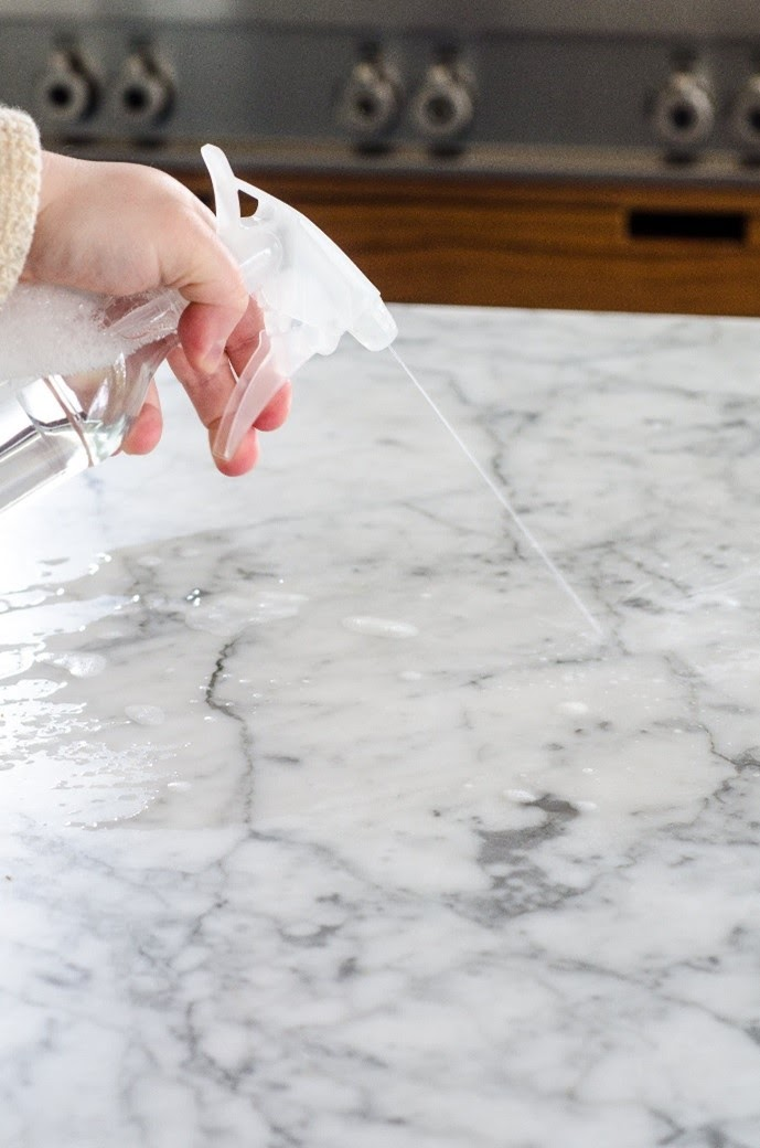 person cleaning a natural stone countertop